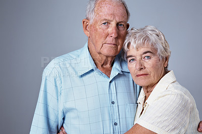 Buy stock photo Studio portrait of an elderly couple against a gray background