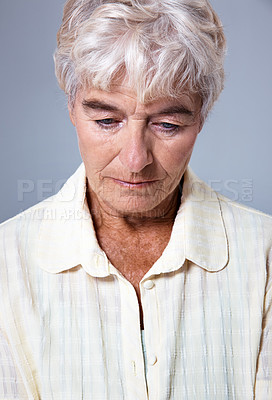 Buy stock photo Studio shot of a depressed senior woman against a gray background