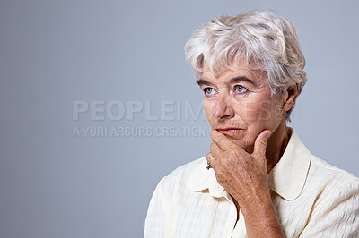 Buy stock photo Studio shot of a sad elderly woman against a gray background