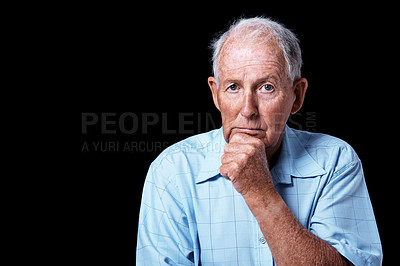 Buy stock photo Studio portrait of a sad-looking elderly man with his hand on his chin isolated on black