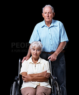 Buy stock photo Studio portrait of an elderly woman sitting in a wheelchair with her husband standing at her side isolated on black