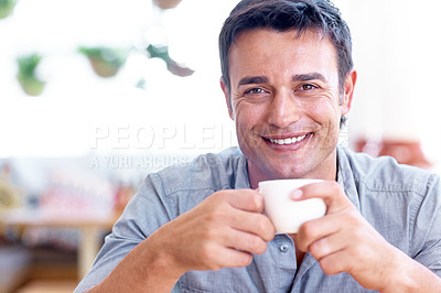 Buy stock photo Shot of a man in a coffee shop holding a cup and smiling