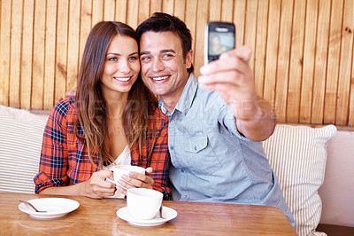 Buy stock photo Shot of a happy couple posing for a selfie with a cellphone