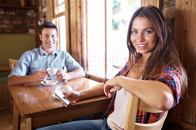Buy stock photo Shot of a couple having coffee while the woman is on her mobile phone