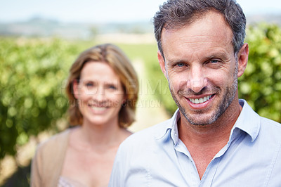 Buy stock photo A smiling mature man with his wife behind him while standing in a vineyard