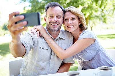 Buy stock photo A happy mature couple having coffee together while out in a garden cafe while using a smartphone