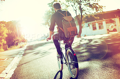 Buy stock photo Rearview shot of a young man riding a bicycle outdoors