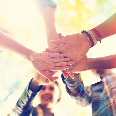 Buy stock photo A group of friends standing in a huddle with their hands piled
