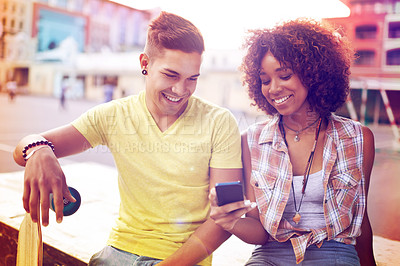 Buy stock photo A young couple looking at something on a cellphone while out skateboarding