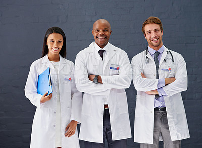 Buy stock photo Portrait of three doctors standing against a gray background