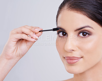 Buy stock photo Shot of a beautiful young woman applying mascara to her lashes