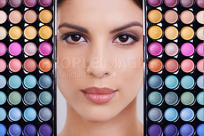 Buy stock photo Studio shot of a beautiful woman with makeup palettes in front of her face