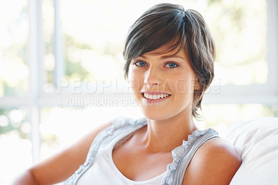 Buy stock photo Smiling young woman relaxing on sofa