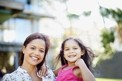 Buy stock photo A cute little girl being held by her mom while standing in the garden