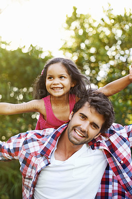 Buy stock photo An attractive young father piggybacking his young daughter with a smile