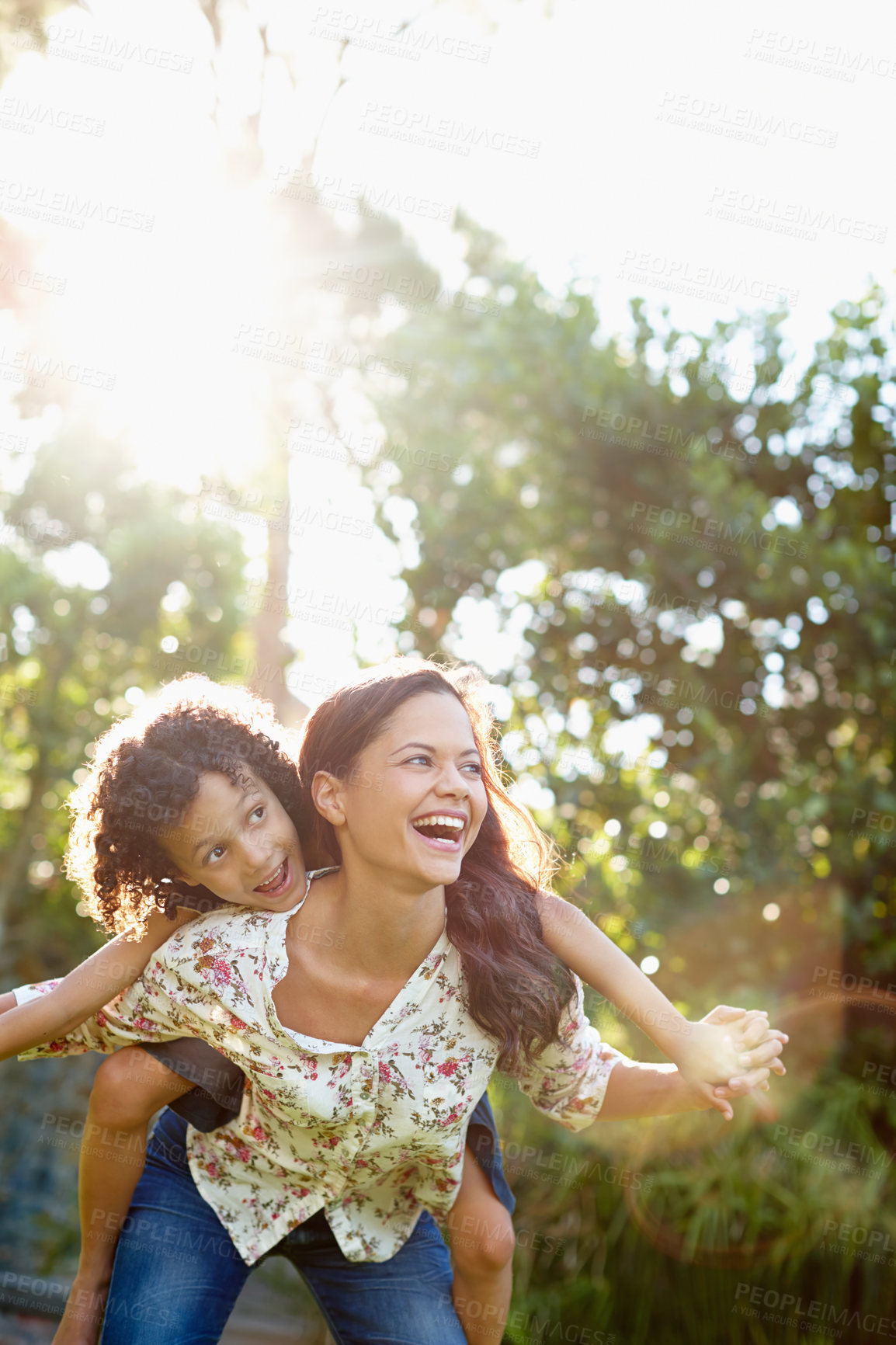 Buy stock photo A young mother piggybacking her son in the park