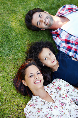 Buy stock photo A cute young family spending time on the grass in the park together