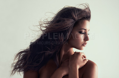 Buy stock photo Studio shot of a gorgeous young woman posing topless against a grey background