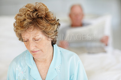 Buy stock photo Shot of an upset-looking senior woman sitting in bed with her husband in the background
