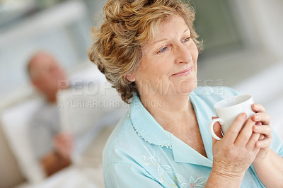 Buy stock photo Shot of a senior woman drinking coffee with her husband lying in bed behind her