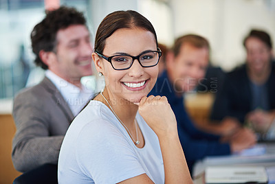 Buy stock photo Portrait of a smiling young woman sitting at a table with colleagues in the background