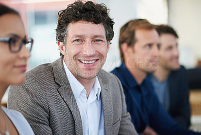Buy stock photo Portrait of a group of business people sitting in a row at a table