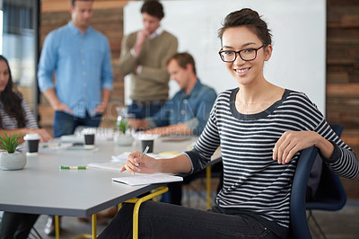 Buy stock photo Portrait of an attractive young woman sitting in an office with colleagues in the background