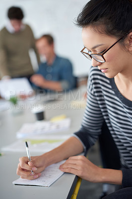 Buy stock photo Shot of an attractive young woman working in an office with colleagues in the background