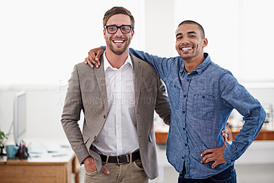 Buy stock photo Shot of two colleagues standing arm in arm in an office