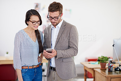 Buy stock photo Shot of two coworkers standing in an office looking at a digital tablet