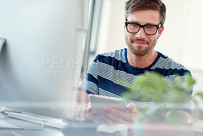 Buy stock photo Portrait of a casually-dressed young man using a digital tablet at his desk
