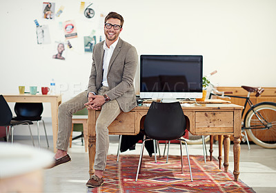 Buy stock photo Portrait of a casually-dressed young man sitting on his desk in an office