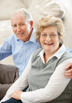 Buy stock photo Portrait of a senior couple smiling while sitting on the sofa at home