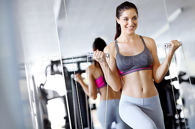 Buy stock photo A beautiful young woman doing weight-training at the gym