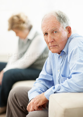 Buy stock photo Portrait of a senior man sitting on the opposite end of a sofa from his wife after an argument