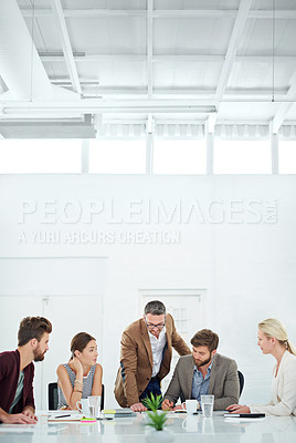 Buy stock photo A group of coworkers standing around a table
