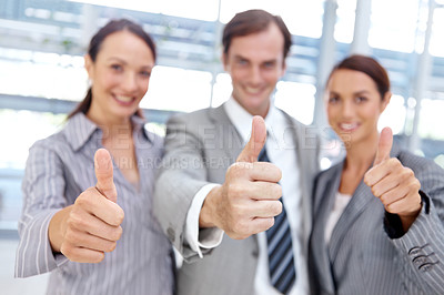 Buy stock photo Three office coworkers standing together and smiling while giving a thumb's up gesture - portrait