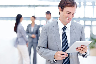 Buy stock photo Smiling young businessman using his digital tablet with a smile