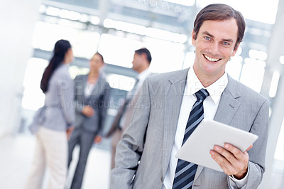 Buy stock photo Smiling young businessman using his digital tablet with a smile - portrait