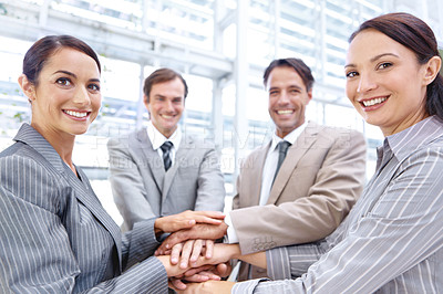 Buy stock photo Group of businesspeople putting their hands in together to show solidarity while smiling