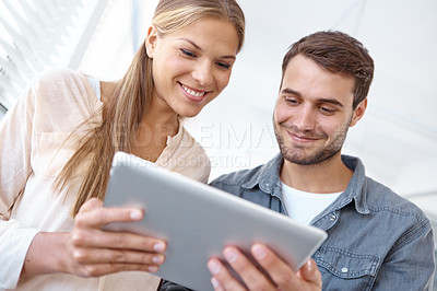 Buy stock photo Low angle shot of two young office workers looking at a digital tablet together
