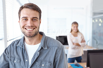 Buy stock photo Portrait of a handsome young design professional with a female colleague standing in the background