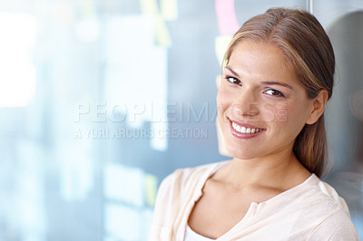 Buy stock photo Portrait of a young business professional leaning against a glass wall and smiling at the camera