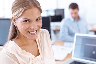 Buy stock photo Closeup portrait of an attractive young designer sitting at her laptop with a male coworker in the background