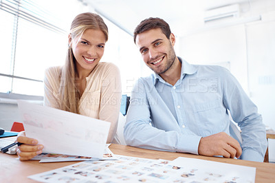 Buy stock photo Portrait of two young design professionals sitting at a table and editing photographs