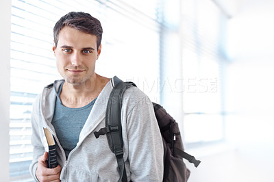 Buy stock photo Portrait of a handsome university student carrying a book and wearing a backpack standing in a hallway