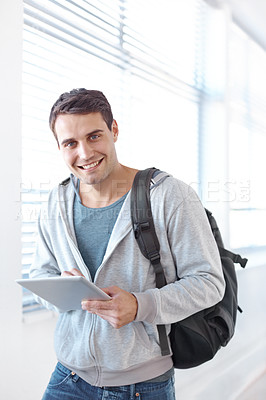 Buy stock photo Portrait of a male university student standing in a hallway working on a digital tablet