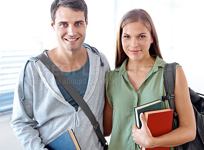 Buy stock photo Portrait of a couple of university students standing arm in arm in a hallway