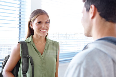 Buy stock photo Cropped shot of two university student talking to each other in a hallway