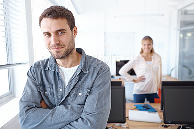 Buy stock photo Handsome young businessman smiling with his arms folded while his colleague stands behind him
